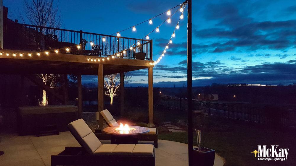 outdoor bistro string lights create a nice soft ambiance around an outdoor fire pit | McKay Landscape Lighting - Omaha, Nebraska
