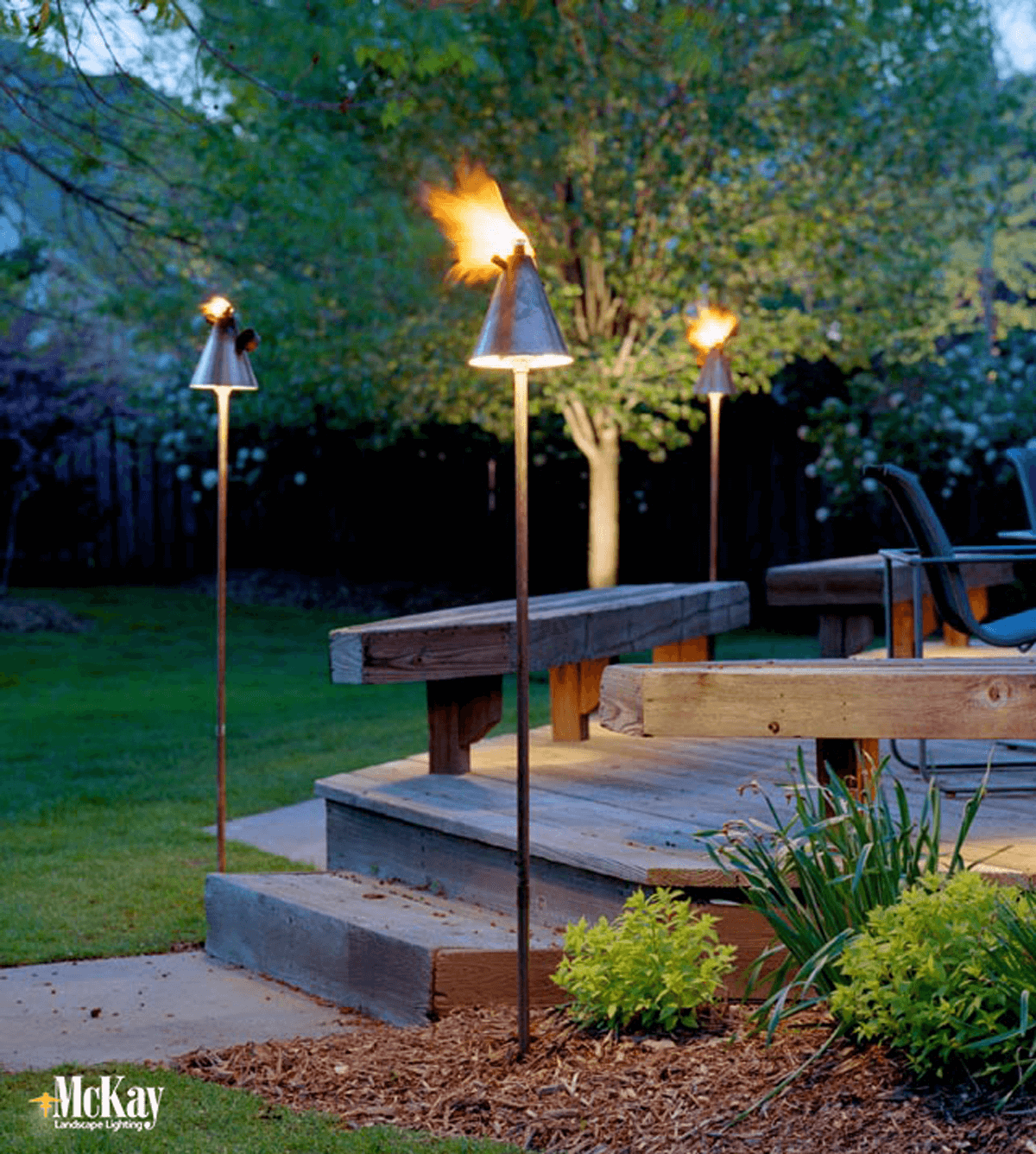 Tiki torches add a fun, resort-style aspect to your outdoor living area. Click to learn more... | McKay Landscape Lighting Omaha Nebraska