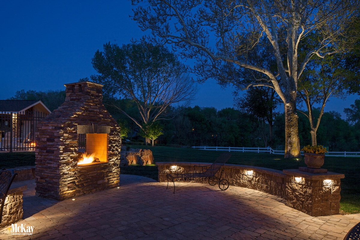 Patio seat wall lights around outdoor fire place | McKay Landscape Lighting Omaha Nebraska