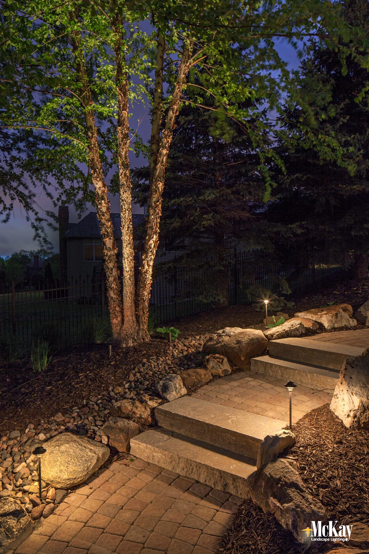 Lighting walkways and paths provide enough illumination to safely guide homeowners and guests around your property and helps prevents trips and falls. Click to learn more about path lighting... | McKay Landscape Lighting Omaha Nebraska