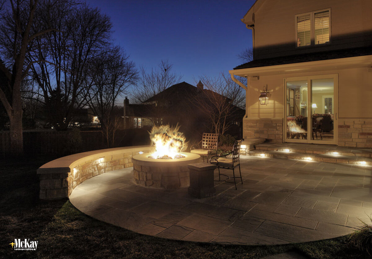 Fire pit seat wall lighting adds a great dimension to your outdoor space after the sun has set. Click to learn more... | McKay Landscape Lighting Omaha Nebraska