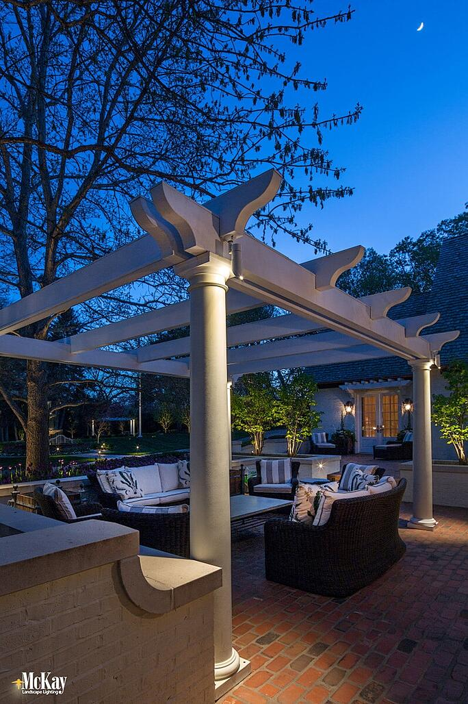 The outdoor pergola lighting elegantly enhances the structure while offering endless opportunities for entertaining or relaxing into the evening.  Click to see more fall outdoor lighitng designs   McKay Landscape Lighting - Omaha, Nebraska
