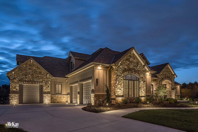 The garage is a prominent portion of the home. Lighting this area helps create balance and it's an easy way to add unique curb appeal. Additionally, a potential intruder could see a dark garage as an opportunity. | Learn more about this garage lighting design by McKay Landscpae Lighting