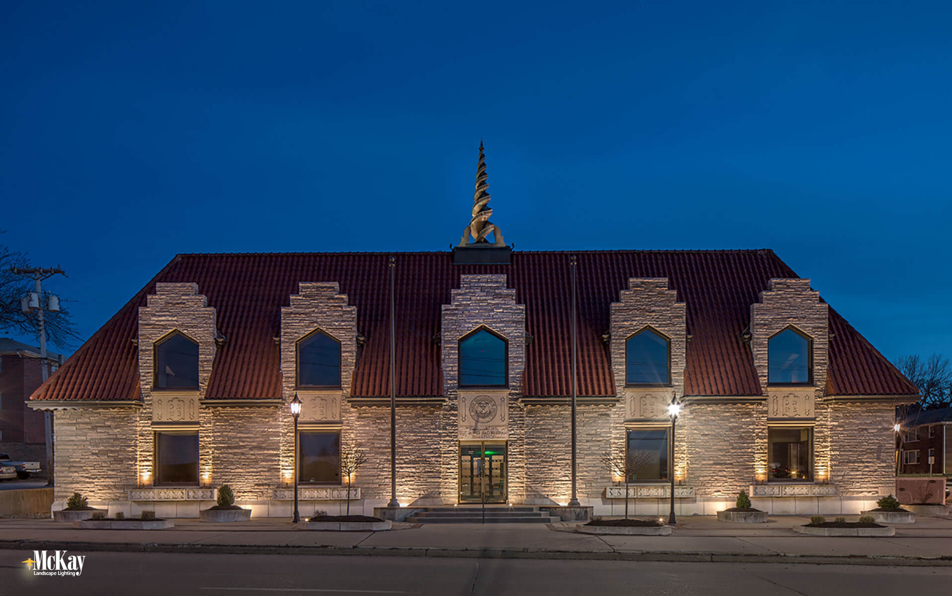 To enhance the property's curb appeal, our designers helped match the color temperature of the pole lights with the landscape lighting on the building. Learn more about the commercial landscape lighting design... | McKay Lighting - Omaha, Nebraska