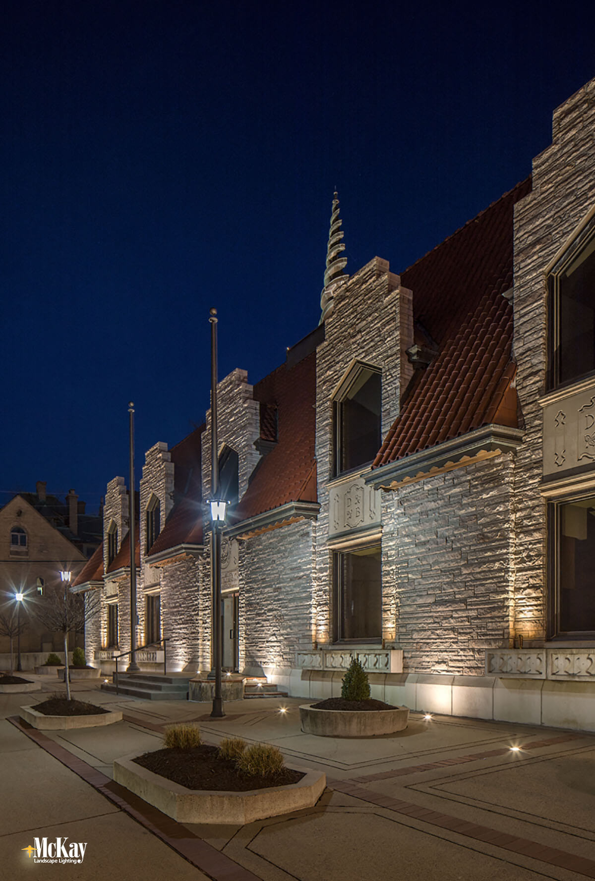 To evenly illuminate the facade and enhance the architecture of the two-story building, we used a combination of well lights and spotlights. Learn more about the commercial landscape lighting design... | McKay Lighting Omaha Nebraska