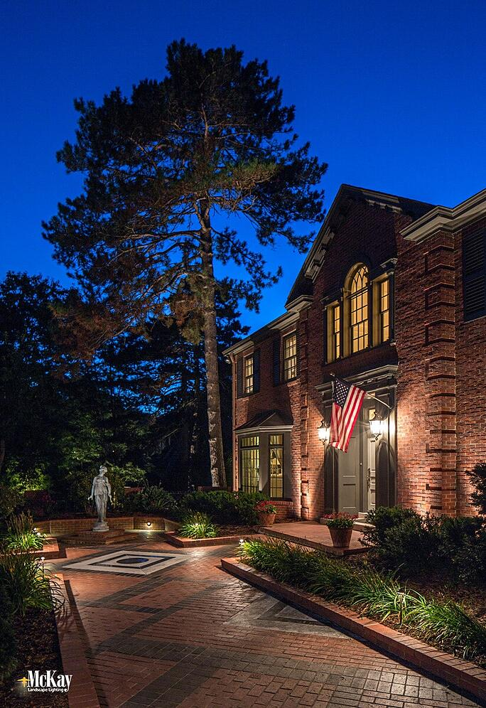 Low-voltage LED landscape lighting creates a subtle and noticeable impact as required by the flag code without overpowering the American flag. Learn more about the American flag lighting requirements. | McKay Landscape Lighting Omaha Nebraska