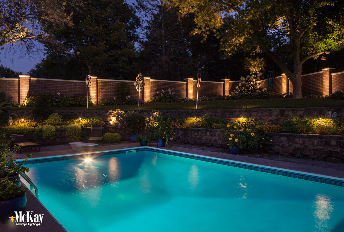 Increase the security of your pool at night by strategically lighting the edges of your yard. | McKay Landscape Lighting Omaha Nebraska