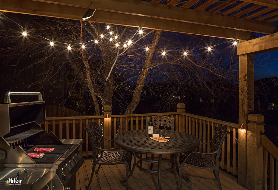 Bistro Outdoor String Lights: When added to a deck or patio, these versatile café inspired outdoor lights produce a soft glow and unique ambiance.  Click to see more deck & patio lighting ideas... McKay Landscape Lighting - Omaha, Nebraska