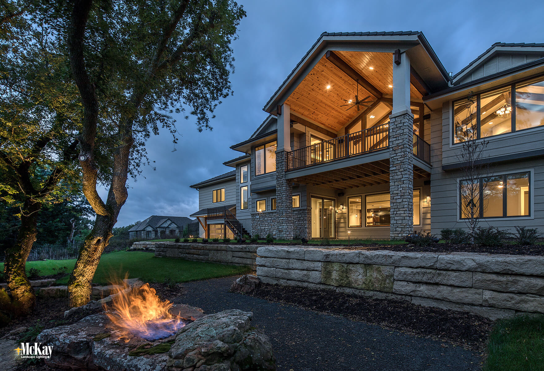 Backyard Outdoor Lighting: The tree lighting creates ambient light to help with visibility when the fire feature is off. It also provides a nice backdrop when the homeowners are looking out from the patio or deck. Click to learn more...   McKay Landscape Lighting - Omaha Nebraska