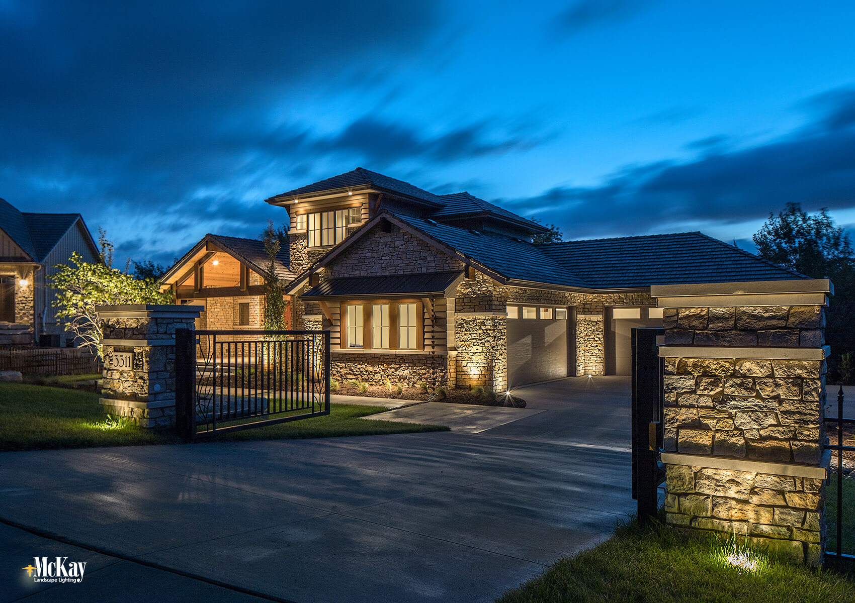The gate lighting provides the property with an extra level of security. The two well lights in the turf grass help accent the stone and brick columns, make the address more noticeable and create ambient light. Click to learn more... | McKay Landscape Lighting - Omaha Nebraska