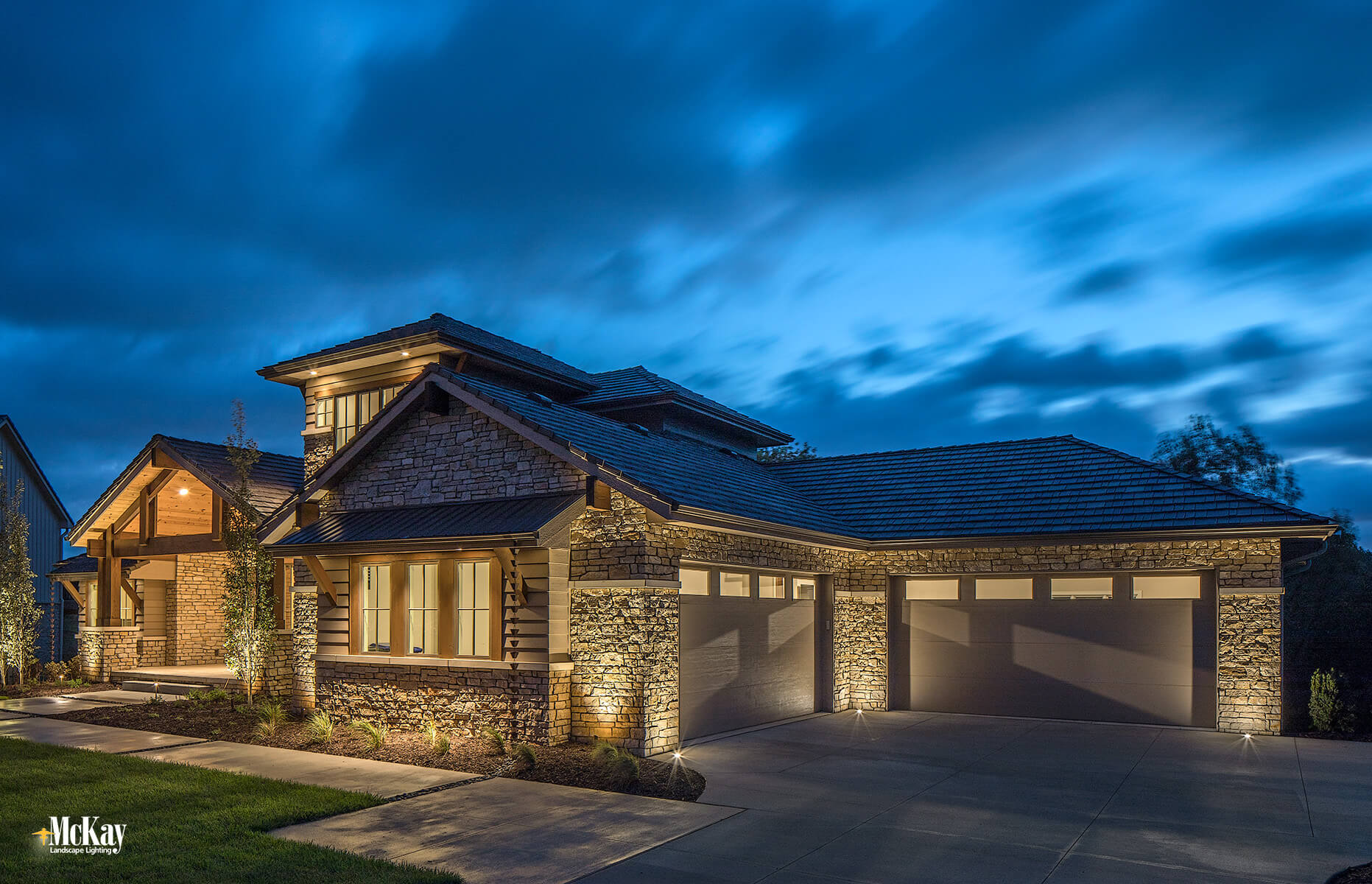 The home has a front and side load garage. This area isn't noticeable from the front of the house or inside of the home, but becomes the main focal point when you enter into the driveway.  Outdoor garage security lighting provides a comprehensive overall look and creates balance with the rest of the house. Click to learn more...   McKay Landscape Lighting - Omaha Nebraska