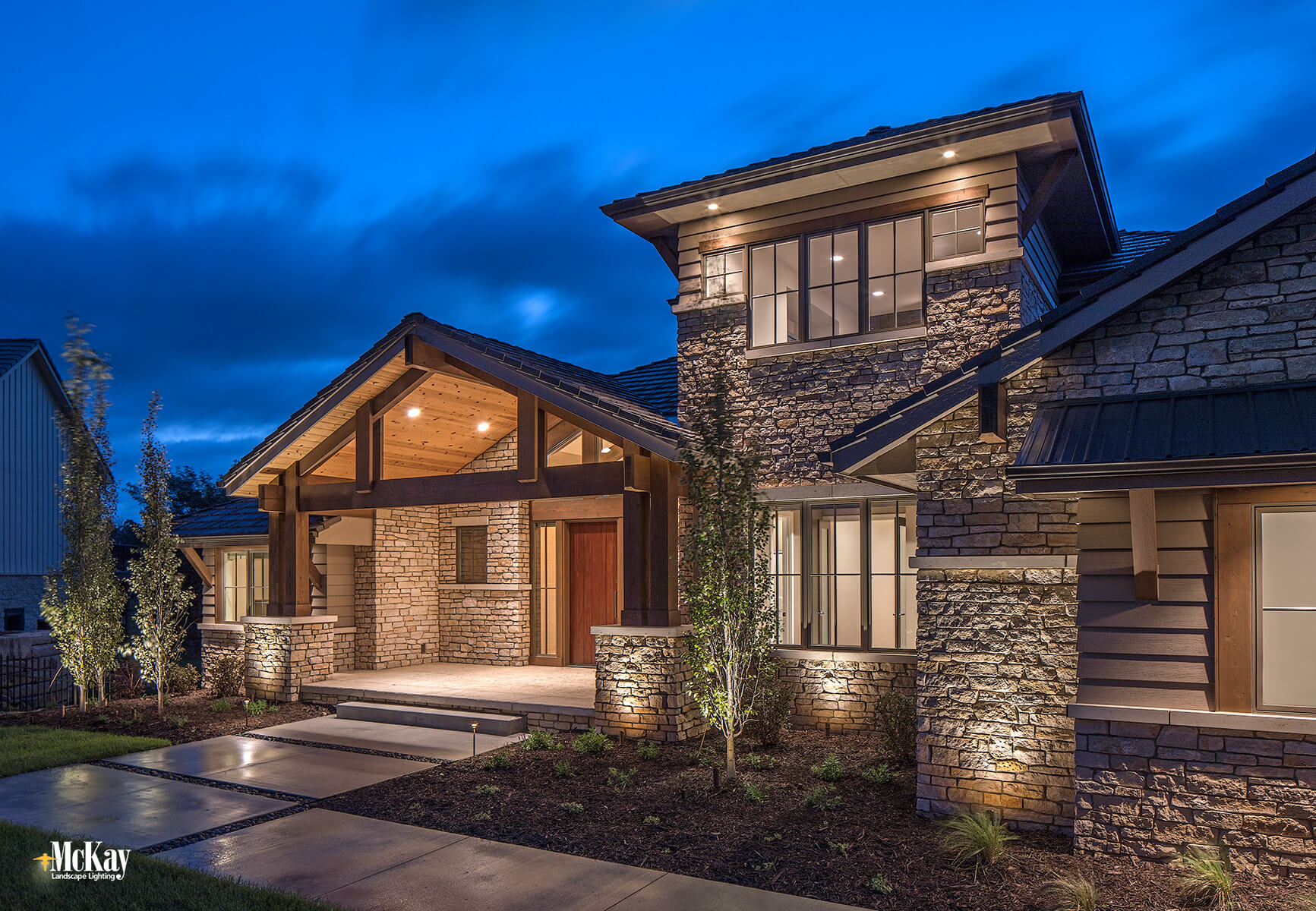 Placing lights on either side of the porch elegantly illuminate the stonework and wood detailing while marking the front entry at the same time.  Click to learn more about the landscape lighting design...   McKay Lighting - Omaha Nebraska