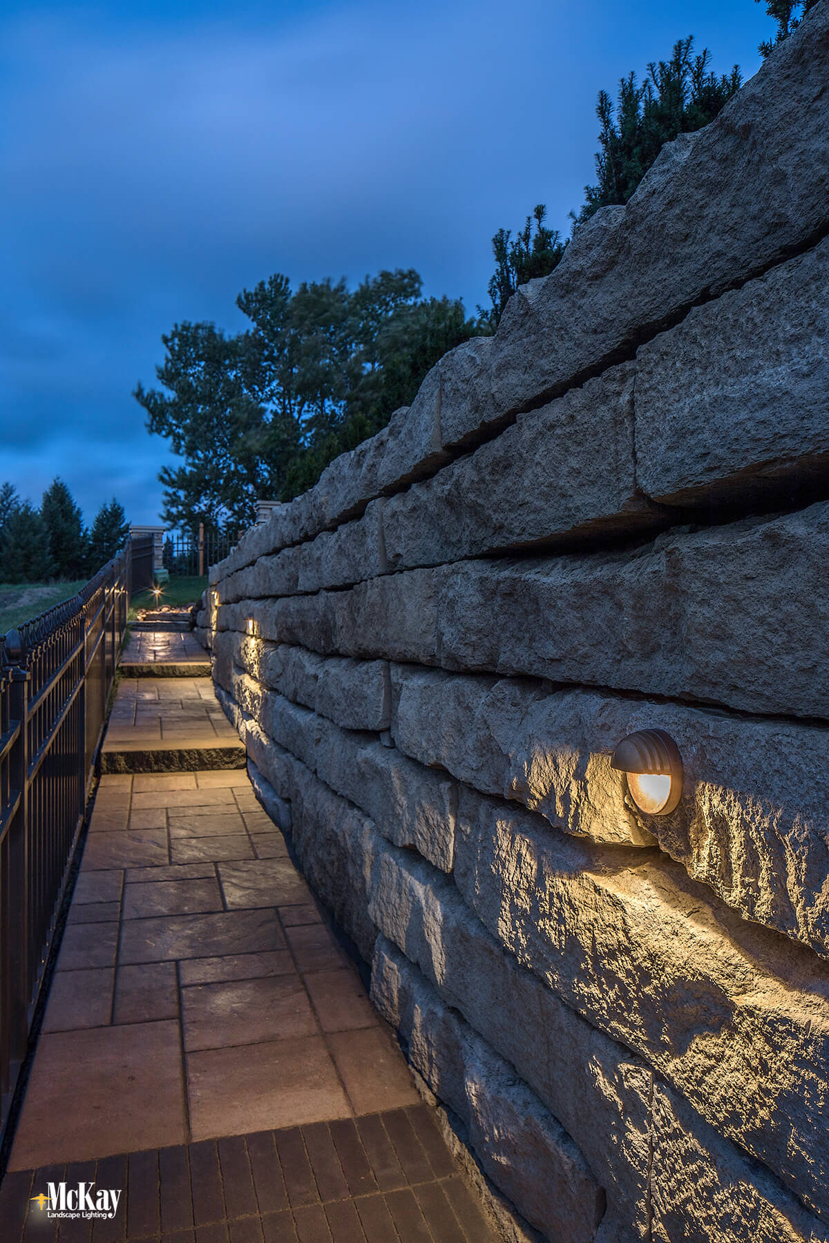 Retaining Wall Outdoor Lighting: These wall lights sit flush with the stone and effectively spread light down and out to light the path. The elevation changes as you walk. We installed a light at each step tread to help note each change in elevation. Click to learn more...   McKay Landscape Lighting - Omaha Nebraska