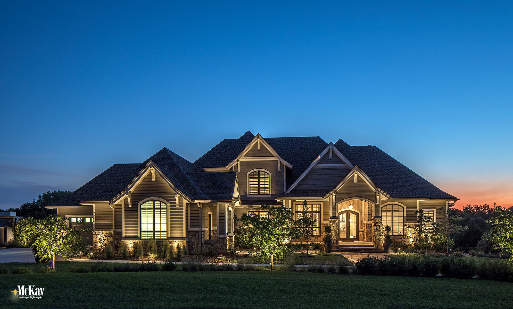 There's nothing quite like driving up to a warm, welcoming home with the prettiest Nebraska sunset peeking through the trees in the backdrop. This gorgeous new home is nestled in a serene location outside of Omaha, surrounded by the wonders of nature and picturesque views. Click to learn more about the residential landscape lighting design... | McKay Lighting - Omaha, Nebraska