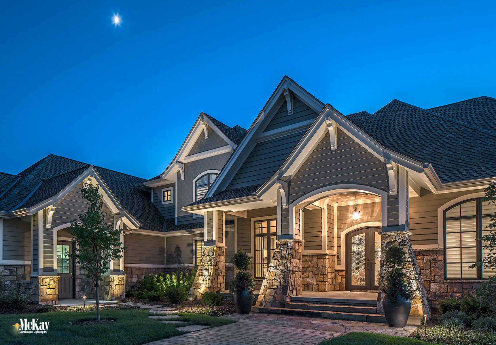 The home's lovely natural stone and decorative corbel peaks are just some of its timeless characteristics that we wanted to highlight at night. Click to learn more about the outdoor lighting design... | McKay Landscape Lighting - Omaha, Nebraska