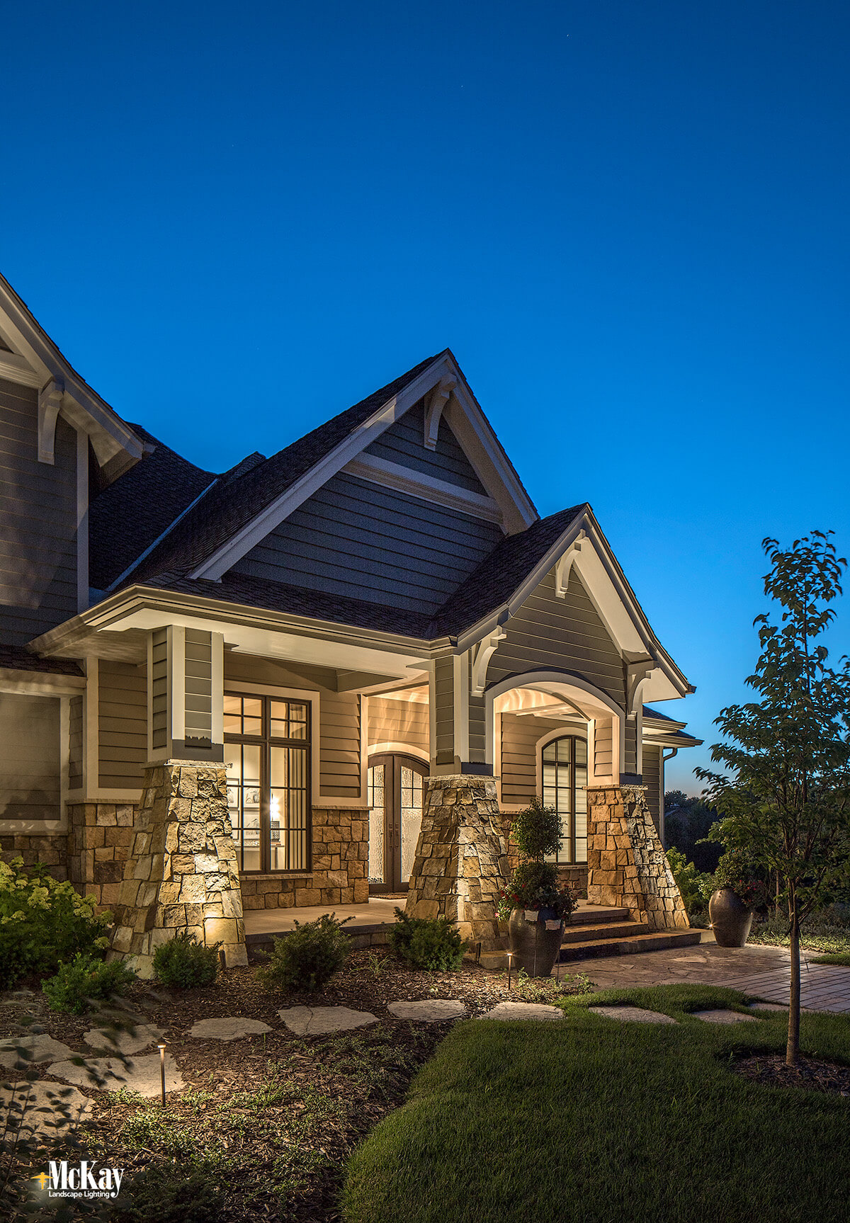 Thoughtful fixture placement at the base of the home lets the light gently crawl up the stonework and creates interesting shadows while evenly illuminating the front peaks. Click to learn more about the outdoor lighting design... | McKay Landscape Lighting - Omaha, Nebraska