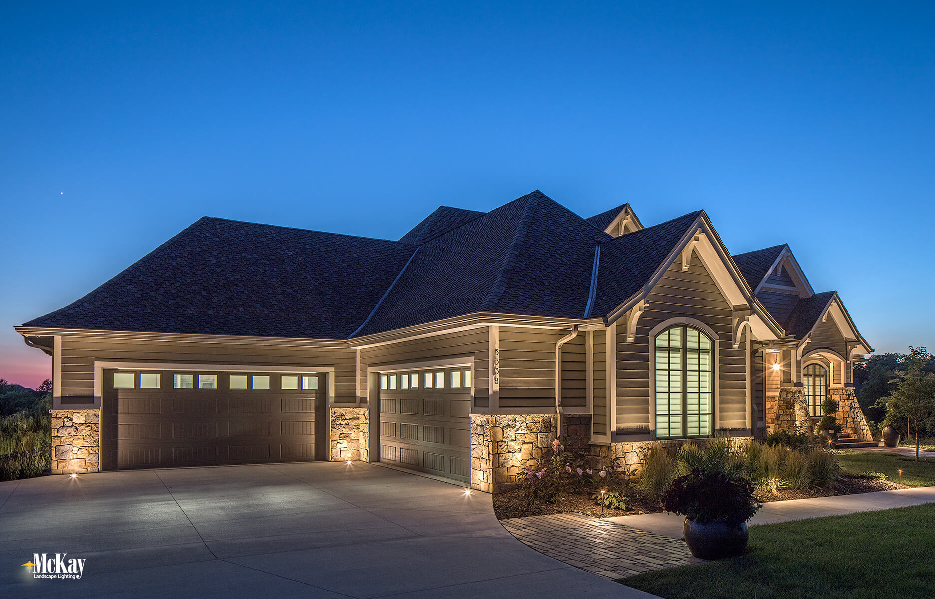 The garage is off to the side and not visible from the front door. Without light, the garage would be very dark and would have left the homeowners vulnerable. Click to learn more about this outdoor lighting design... | McKay Landscape Lighting - Omaha, Nebraska