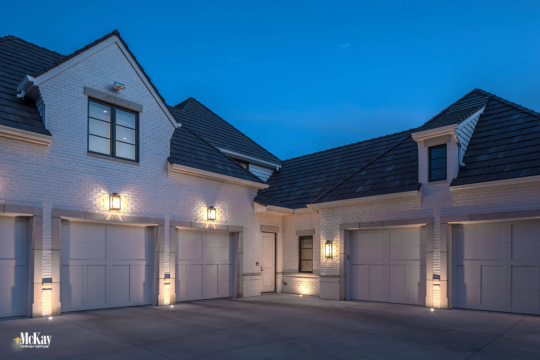 In-ground well lights are a great option because it beautifully illuminates and enhances while increasing the security of the garage. Click to read more... | McKay Landscape Lighting - Omaha, Nebraska