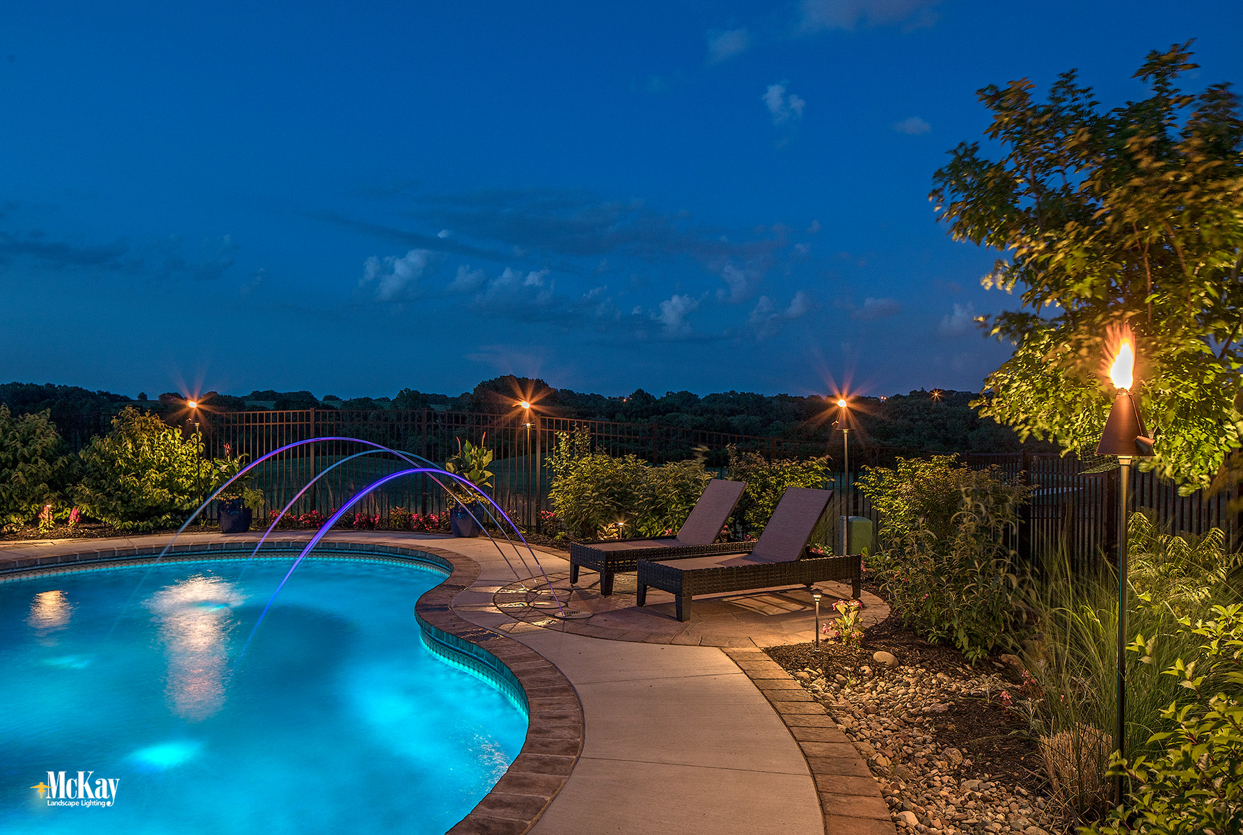 High-End Tiki Torches provide a vacation-like feel around pools. Learn more about pool lighting... | McKay Landscape Lighting - Omaha, Nebraska